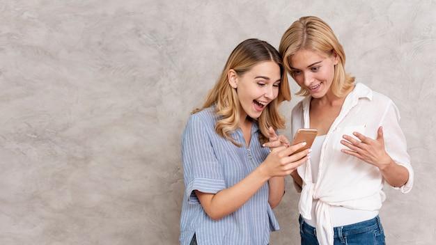 Moças bonitas que verificam uma mensagem Foto gratuita