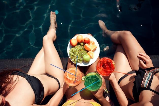 Moças com frutas e coquetéis à beira da piscina Foto Premium