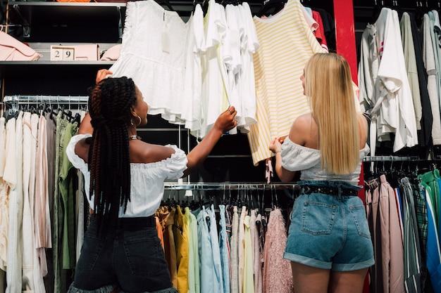 Moças de baixo ângulo, verificando a loja de roupas Foto gratuita