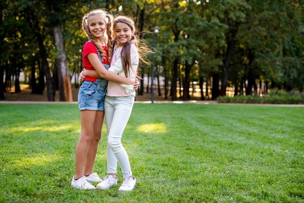 Moças que abraçam o espaço da cópia Foto gratuita