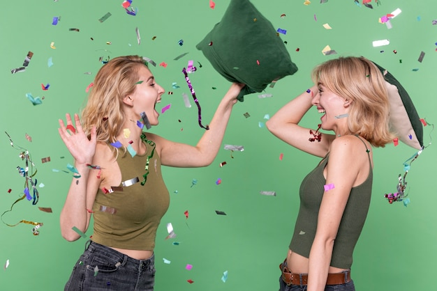 Moças que têm uma luta de almofadas Foto gratuita
