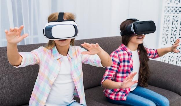 Moças que usam um fone de ouvido da realidade virtual tocando suas mãos no ar Foto gratuita
