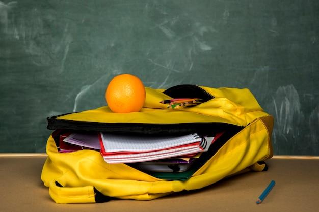 Mochila amarela com cadernos e laranja Foto gratuita