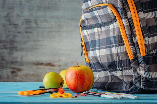 Mochila, apple e material escolar em fundo de madeira Foto Premium