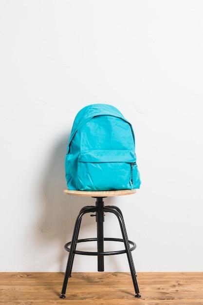 Mochila azul na cadeira de fezes na superfície de madeira Foto Premium