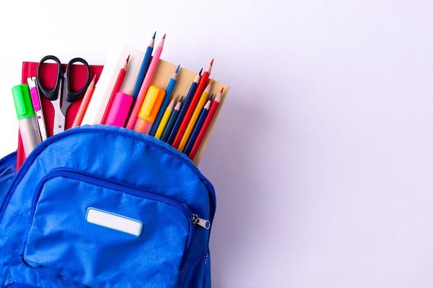 Mochila com diferentes artigos de papelaria coloridos na mesa branca. volta ao conceito de escola. Foto Premium