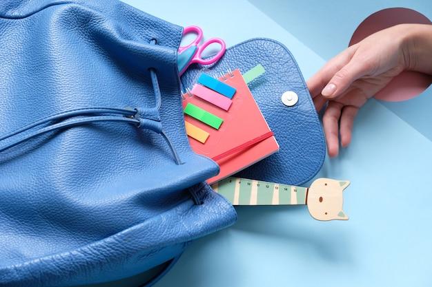 Mochila com diferentes artigos de papelaria coloridos na mesa. Foto Premium
