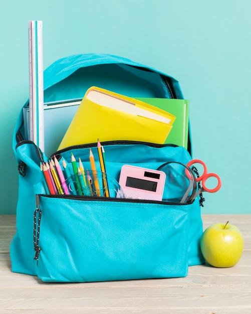 Mochila escolar azul com suprimentos essenciais Foto gratuita