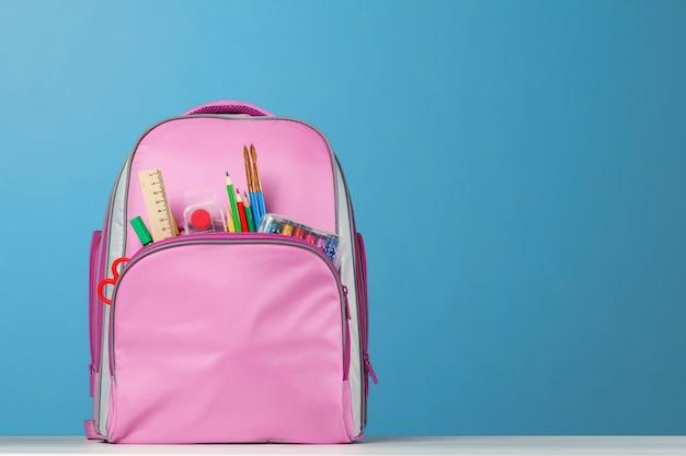 Mochila rosa com material de escritório em cima da mesa. Foto Premium