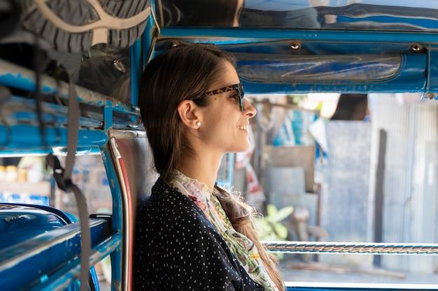 Mochileiro da mulher que viaja no transporte público em tailândia. songthaew é uma maneira barata de viajar entre os países asiáticos. experiência turística no verdadeiro sudeste da ásia. feriados e conceito de viagens. Foto Premium