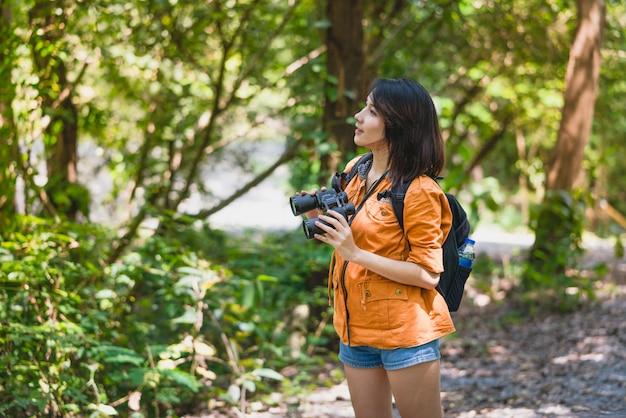 Mochileiro de jovem mulher asiática com telescópio binóculos olhando pássaros na floresta em férias de férias no verão, viagens de aventura Foto Premium