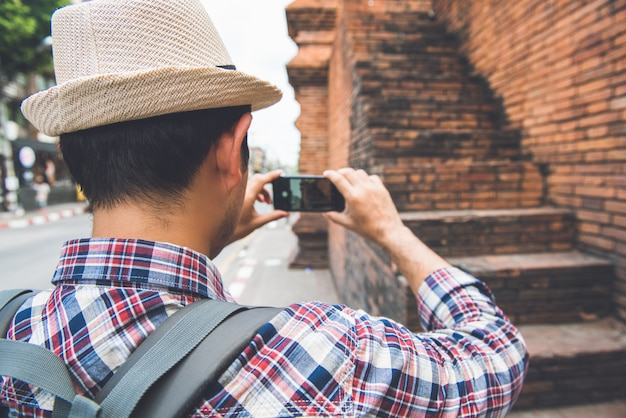 Mochileiro de turista masculino asiático tirando foto com o smartphone no tha phae gate, um dos antigos marcos famosos da cidade em chiang mai tailândia Foto Premium