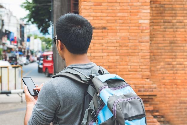 Mochileiro de turista masculino asiático usando smartphone searcing para localização enquanto viaja em tha phae gate, chiang mai tailândia Foto Premium