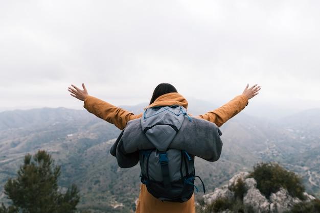 Mochileiro feminino em pé no topo da montanha, amando a natureza Foto gratuita