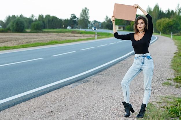 Mochileiro na estrada está segurando uma placa de papelão em branco Foto Premium