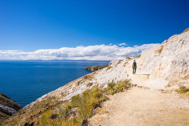Mochileiro que explora as trilhas incas majestosas na ilha do sol, lago titicaca, entre o destino o mais cênico do curso em bolívia. viagens de aventura e férias nas américas. Foto Premium