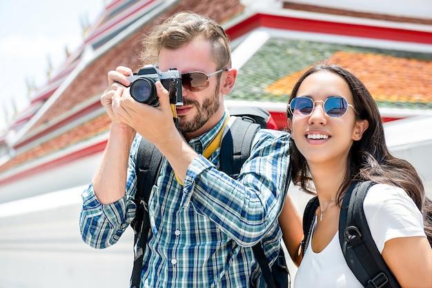 Mochileiros casal de turista tirando fotos enquanto viaja em bangkok tailândia Foto Premium