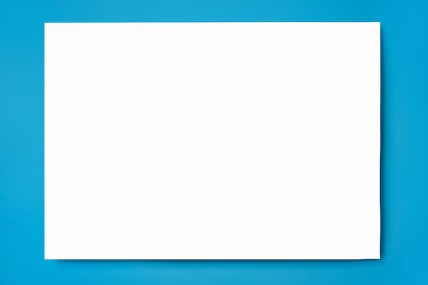 Mock-se de uma folha de papel a4 branco sobre uma superfície azul Foto Premium