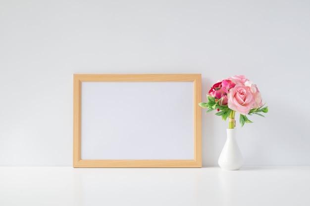 Mock-se moldura com flores na mesa Foto Premium