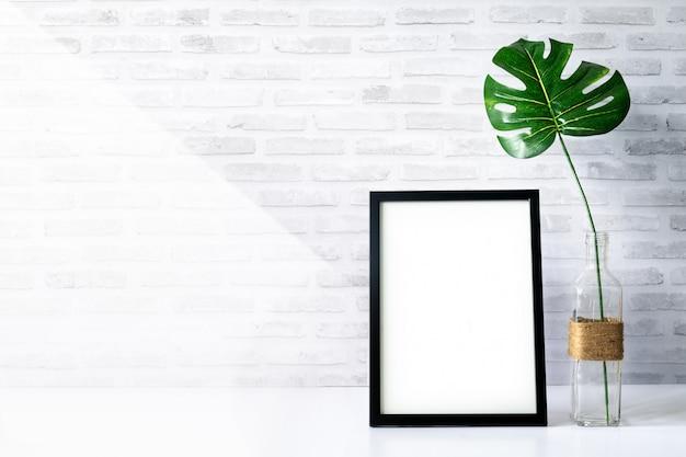 Mock-se moldura de retrato com planta verde na tabl Foto Premium