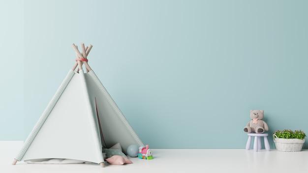 Mock-se na sala de jogos infantil com tenda e mesa sentado boneca na parede azul vazia Foto Premium
