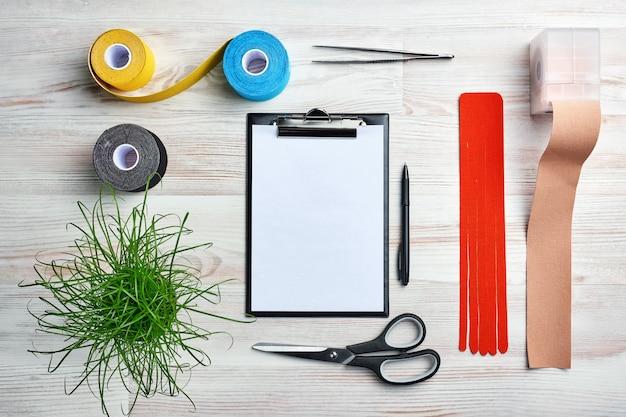 Mock up com prancheta, rolos de fita kinesio colorido, tesoura, pinça e outras ferramentas Foto Premium