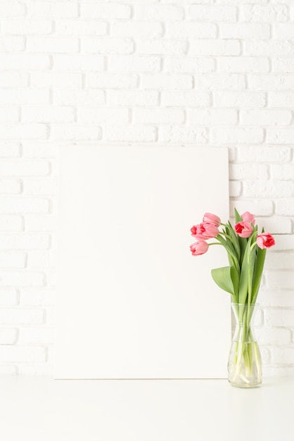 Mock up design. mock-se com moldura e tulipas rosa no fundo da parede de tijolo branco Foto Premium