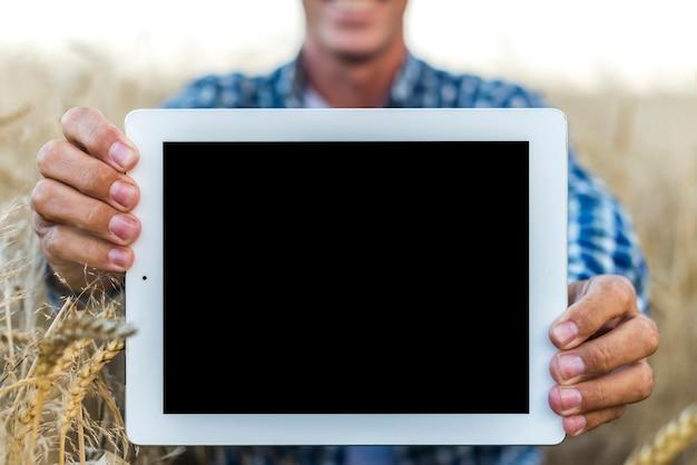 Mock-up homem segurando um tablet Foto gratuita