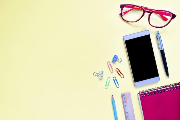 Mock up telefone inteligente e equipamentos de escritório ou acessórios em fundo colorido Foto Premium