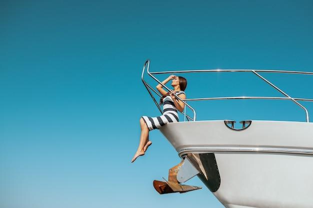 Moda adorável jovem vestido listrado, sentado na beira do iate de luxo e olhando o mar durante a viagem de vela. mulher feliz, aproveitando as viagens de verão. férias ou feriado Foto Premium