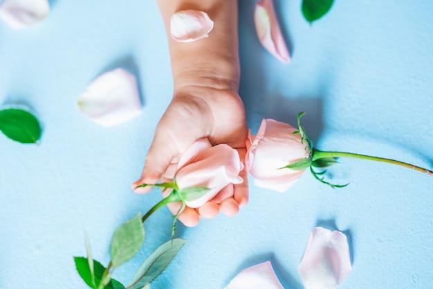 Moda arte mão de uma criança pequena segurando flores sobre fundo azul Foto Premium