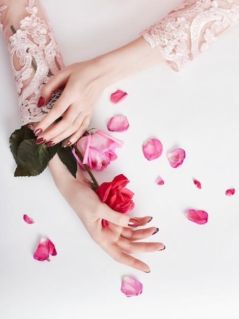 Moda arte retrato mulher verão vestido e flores na mão com uma maquiagem contrastante brilhante. meninas criativas da foto da beleza que sentam-se na tabela em um fundo cor-de-rosa de contraste com sombras coloridas Foto Premium