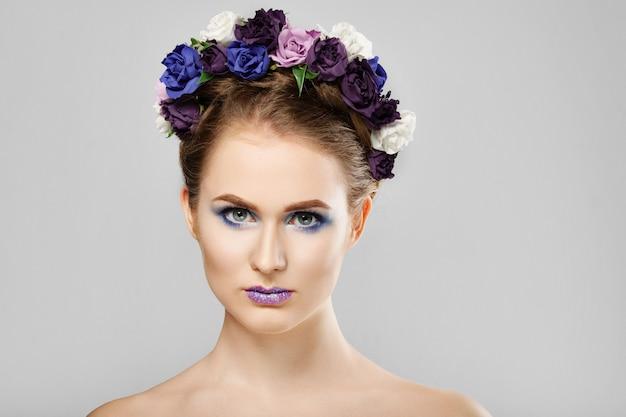 Moda beleza modelo menina com flores no cabelo dela. maquiagem criativa perfeita e penteado de arte floral. Foto Premium