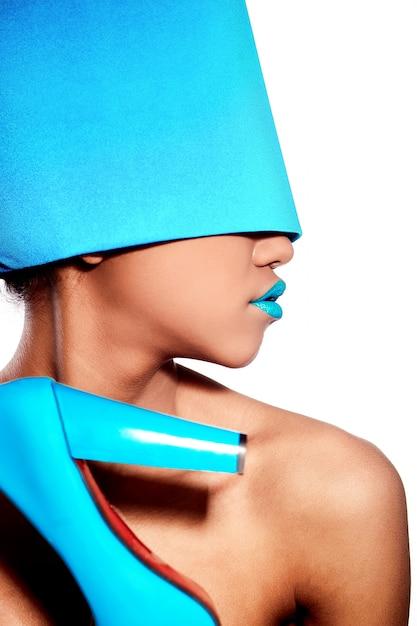 Moda de alta moda look.glamour linda mulher americana negra com lábios azuis brilhantes com material azul na cabeça isolado no branco Foto gratuita