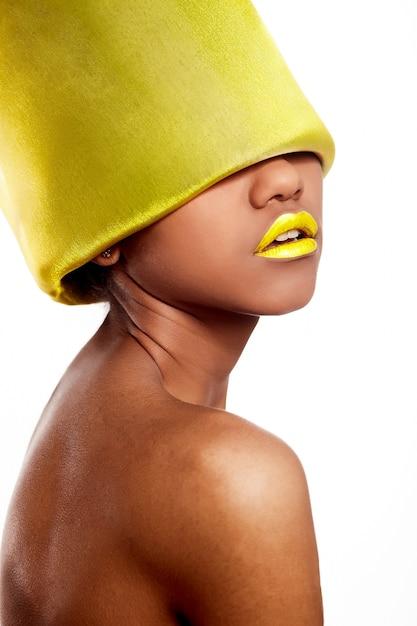 Moda de alta moda look.glamour linda mulher americana negra com lábios brilhantes amarelos com material amarelo na cabeça isolado no branco Foto gratuita