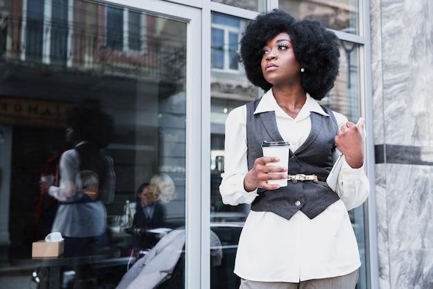 Moda jovem empresária africana segurando a taça de café para viagem e tablet digital olhando para longe Foto gratuita