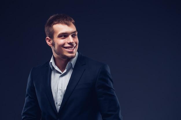Moda jovem empresário terno preto sobre fundo escuro Foto Premium