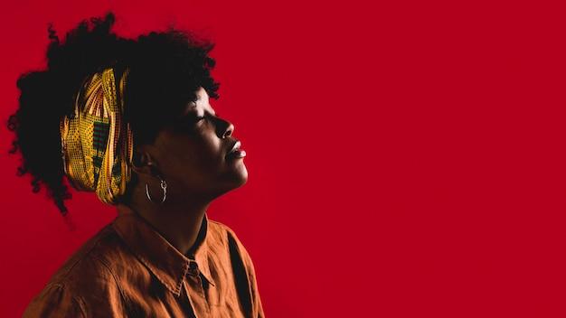 Moda jovem mulher afro-americana encaracolado em estúdio com fundo colorido Foto Premium