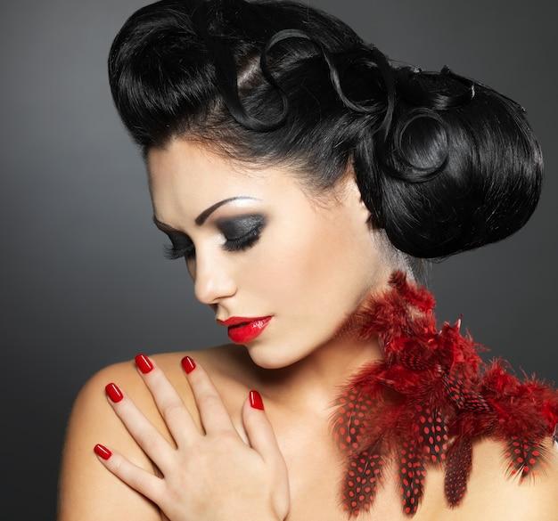 Moda jovem mulher com unhas vermelhas, penteado criativo e maquiagem Foto gratuita