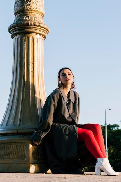 Moda jovem mulher sentada sob o pilar com meia vermelha e calçado branco Foto gratuita