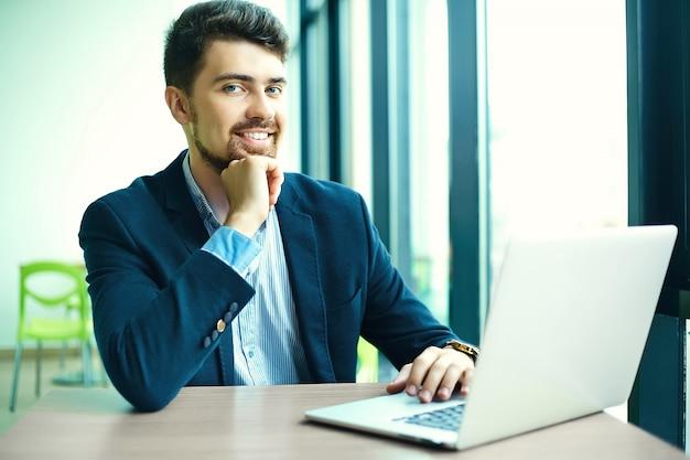 Moda jovem sorridente homem hipster no café da cidade durante a hora do almoço com o notebook no terno Foto gratuita