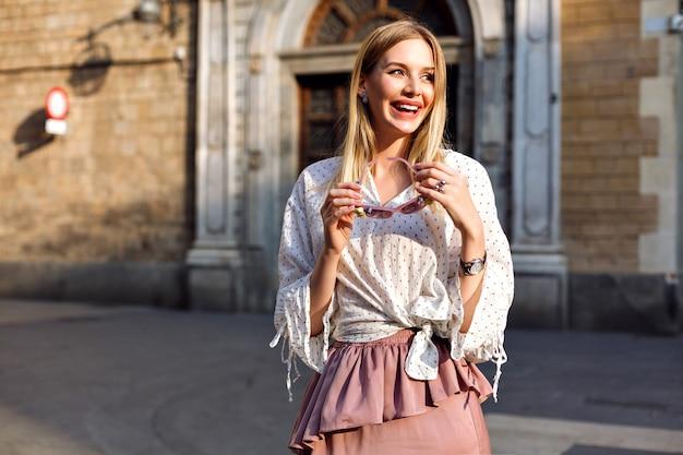 Moda luxo retrato ensolarado de mulher loira posando na rua usando blusa e saia longa de seda Foto gratuita