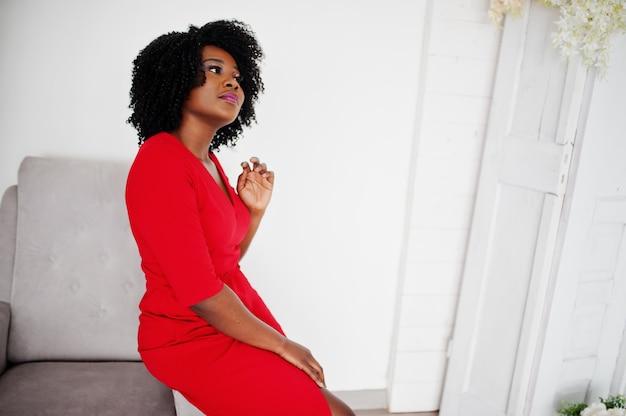 Moda modelo afro-americano em vestido vermelho beleza, mulher sexy, posando de vestido de noite na sala branca vintage. Foto Premium