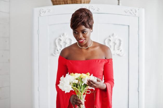 Moda modelo americano africano no vestido vermelho beleza, mulher sexy, posando de vestido de noite segurando flores no quarto branco vintage. Foto Premium