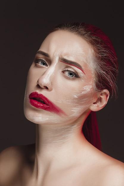 Moda modelo menina com rosto colorido pintado. retrato de arte moda beleza de mulher bonita com maquiagem abstrata colorida. Foto gratuita