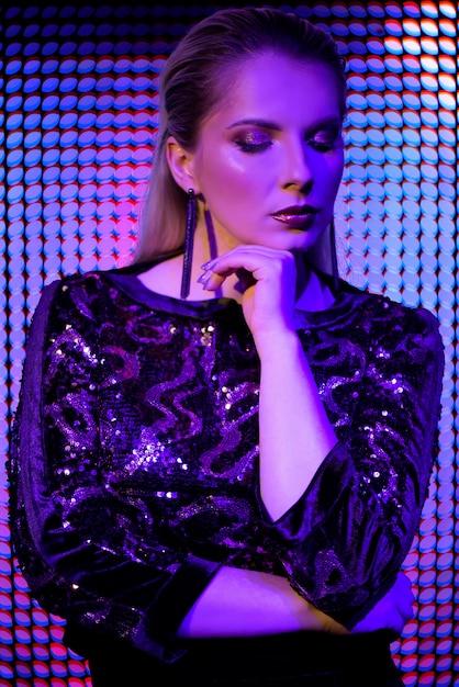 Moda modelo mulher em luzes brilhantes azuis e roxas de néon brilhante colorido uv Foto Premium