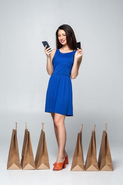 Moda mulher comprando on-line segurando o celular e cartão de crédito com sacolas coloridas isoladas Foto gratuita