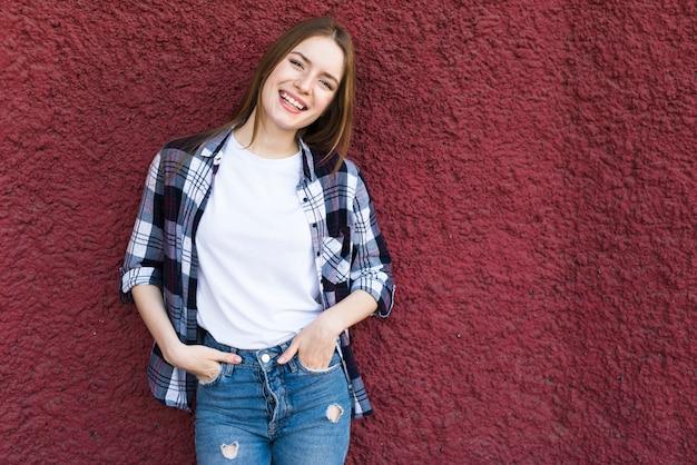 Moda mulher feliz encostado na parede texturizada vermelha Foto gratuita