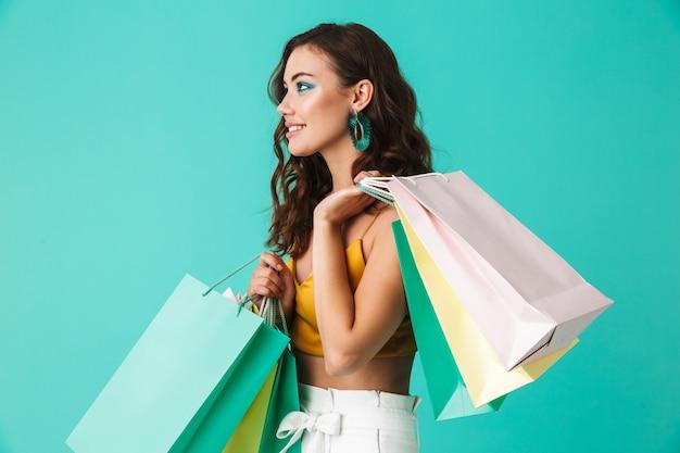 Moda mulher glamourosa usando brincos elegantes carregando sacolas de papel colorido com compras Foto Premium