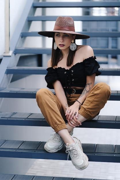 Moda mulher morena com cabelos longos, vestindo elegante chapéu de vime grande, posando nas escadas Foto Premium